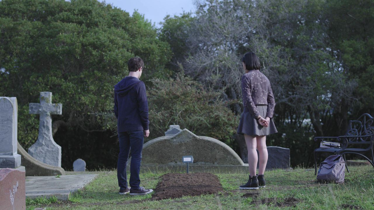 Photo of Clay beside Hannah Baker's grave