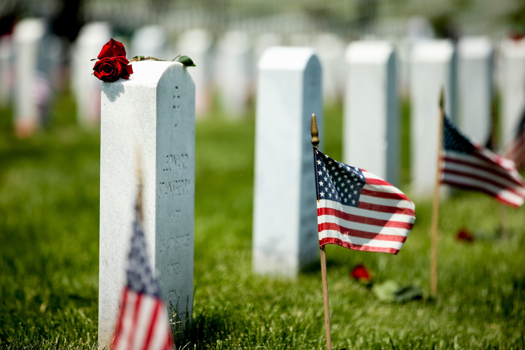 Photo of Rows of Headstones with American flag on