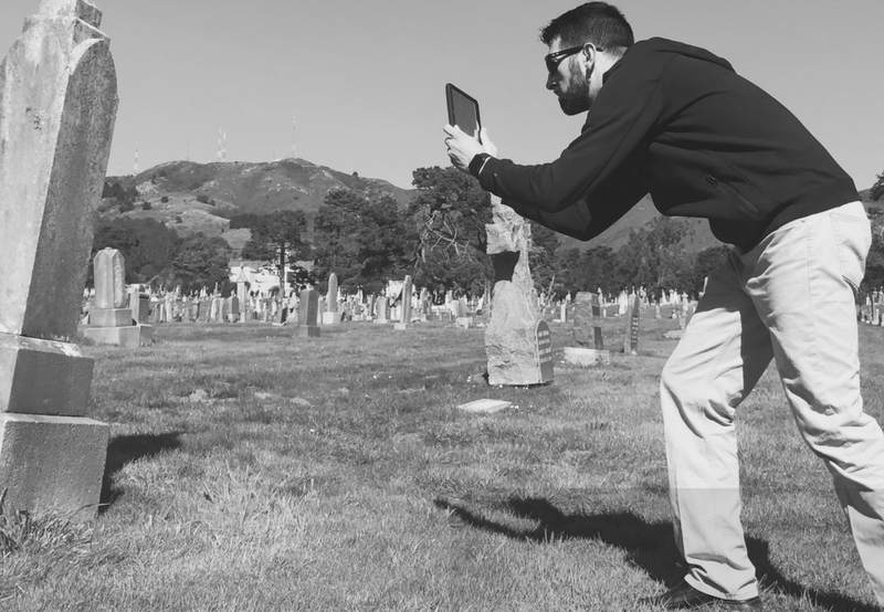 Picture of a man taking a photo of a headstone with a tablet
