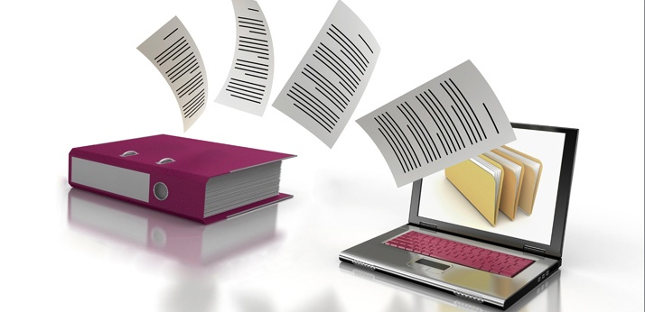 Image of some paper files transferring into a laptop