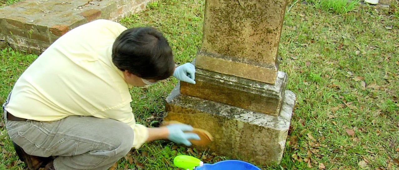 Photo of a man cleaning a headstone