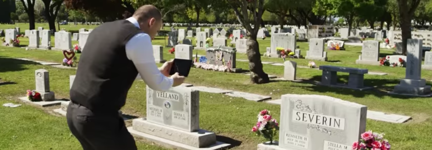 Photo of a man taking a photo of a headstone using a tablet