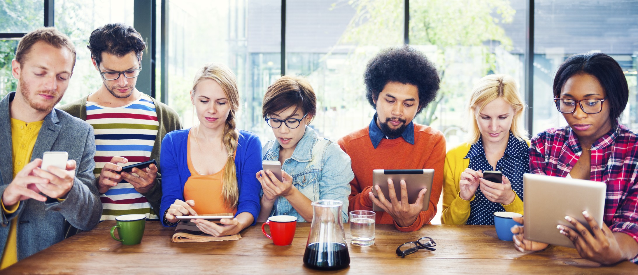 Photo of group of millennials sat at a table all using devices