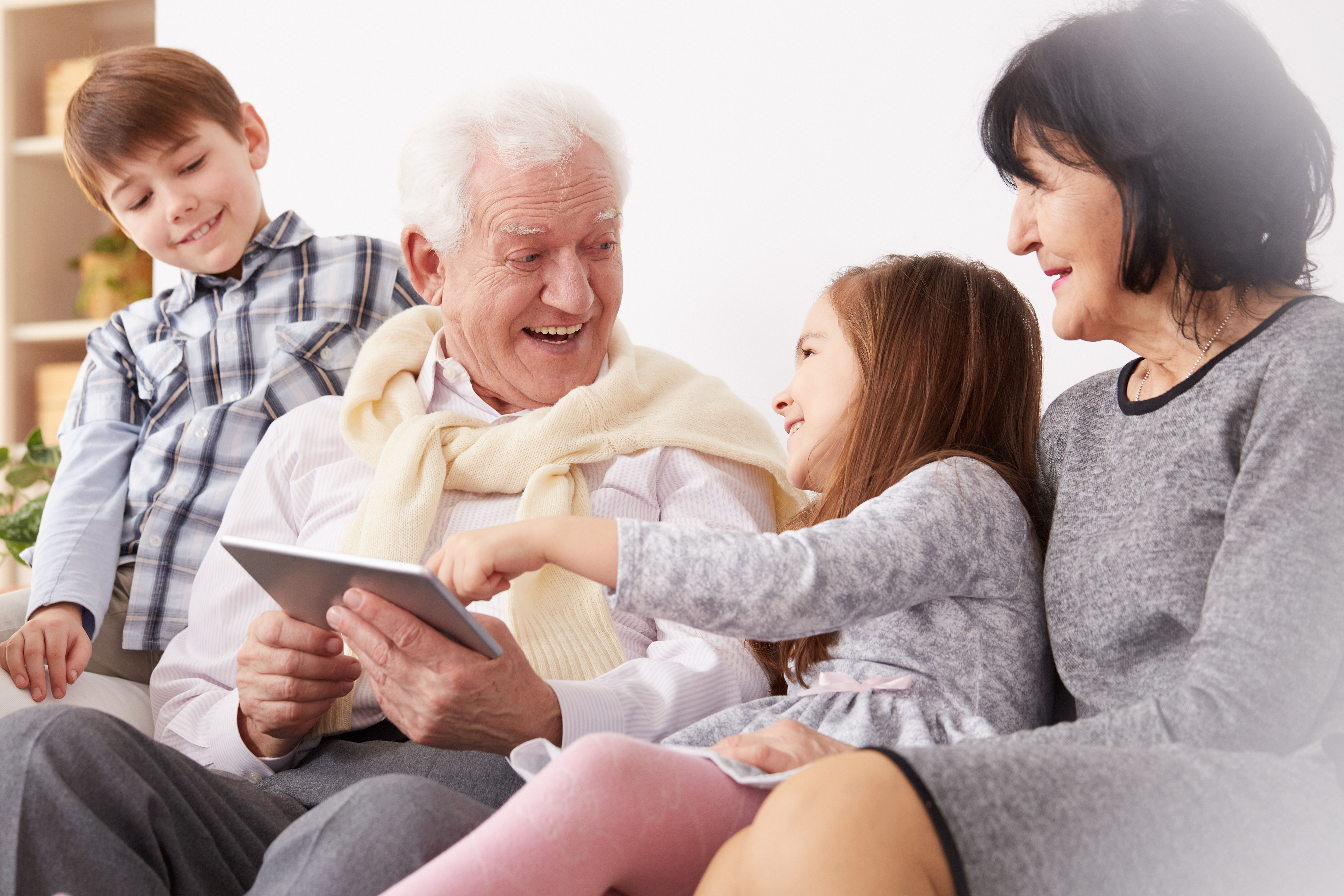 Photo of a family of multiple generations using a tablet